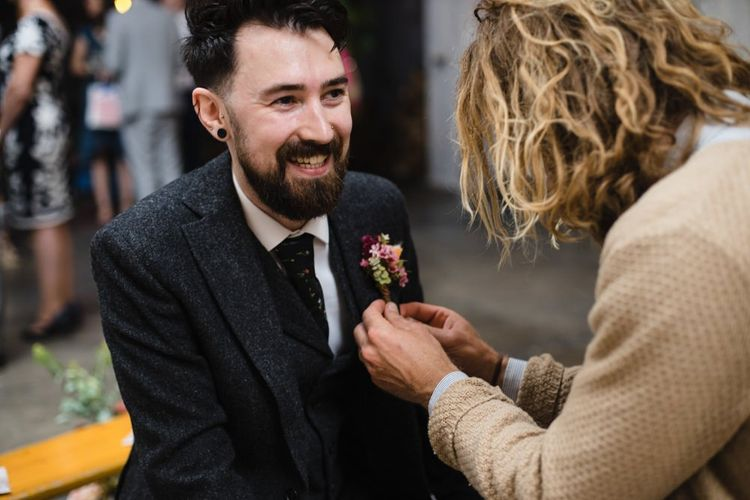 Groom getting ready for wedding ceremony wearing brightly coloured floral buttonhole