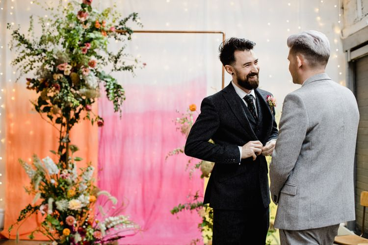 Groom at the top of the aisle with pink, orange and yellow backdrop and copper archway decorated with floral decor