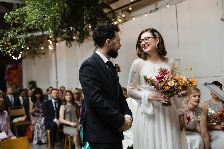 Bride in glasses at industrial wedding ceremony with bright floral bouquet and hanging festoon lighting