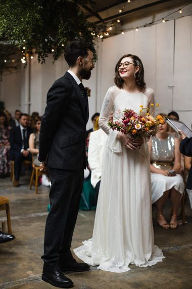 Bride in glasses wearing long sheer sleeved embellished dress and bright floral bouquet