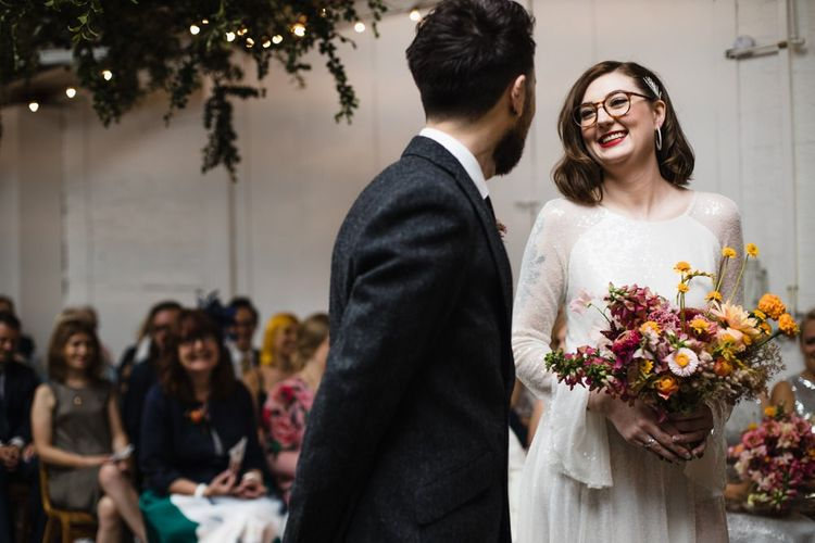 Bride in glasses at industrial wedding ceremony with hanging festoon lighting and bright floral decor