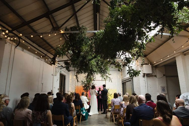 Bride in glasses and groom tie the knot at industrial wedding ceremony with hanging foliage and festoon lighting and