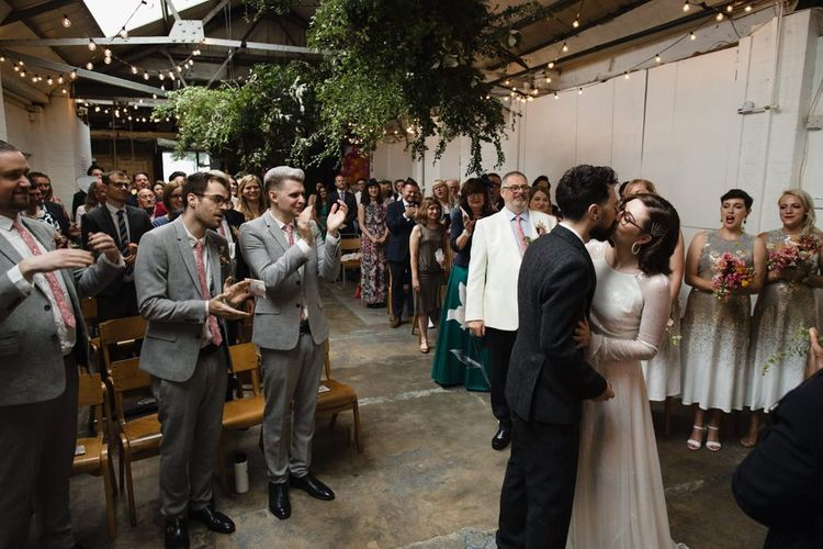 Bride in glasses and groom say 'I do' with their guests at industrial wedding ceremony with festoon lighting and hanging foliage decor
