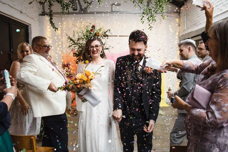 Bride in glasses confetti shot with bright floral bouquet and industrial styling