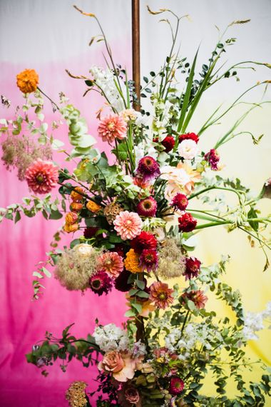 Purple, pink and orange floral decor at industrial wedding with casual styling