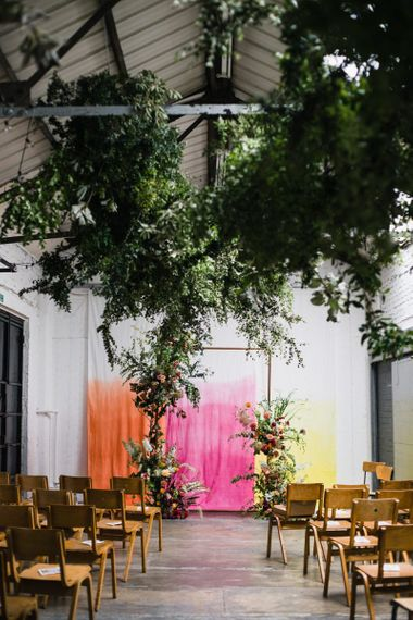 Copper arch with floral decor at industrial wedding ceremony with brightly coloured backdrop