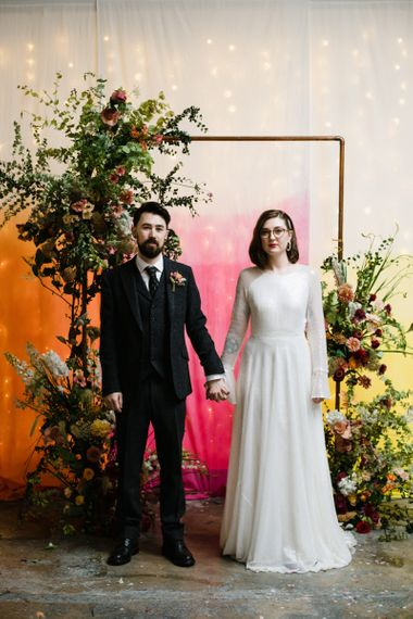 Bride in glasses and groom stood by bright hanging backdrop with copper archway and floral decor
