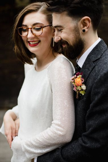 Bride in glasses and long embellished sleeve dress with groom wearing purple and orange floral buttonhole