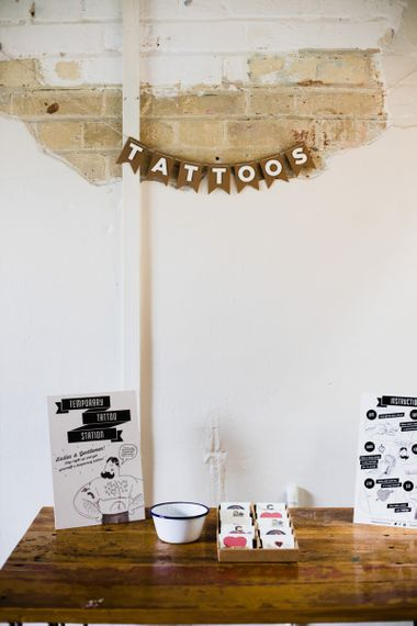 Temporary tattoo station at industrial wedding ceremony hanging sign