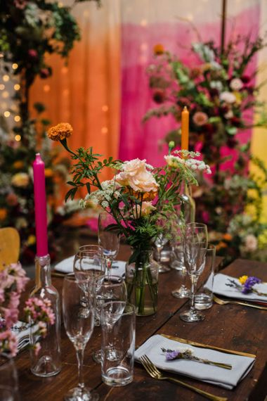 Industrial wedding reception in London with lots of bright floral decor and tall candlesticks