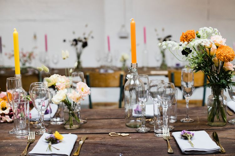 Table settings for industrial wedding reception in London with lots of bright floral decor and tall candlesticks