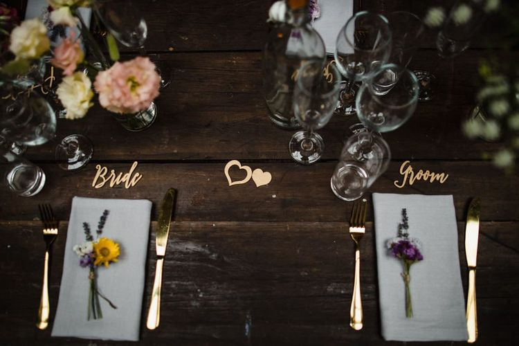 Bride and groom place settings at industrial styled wedding reception with hand tied floral decor