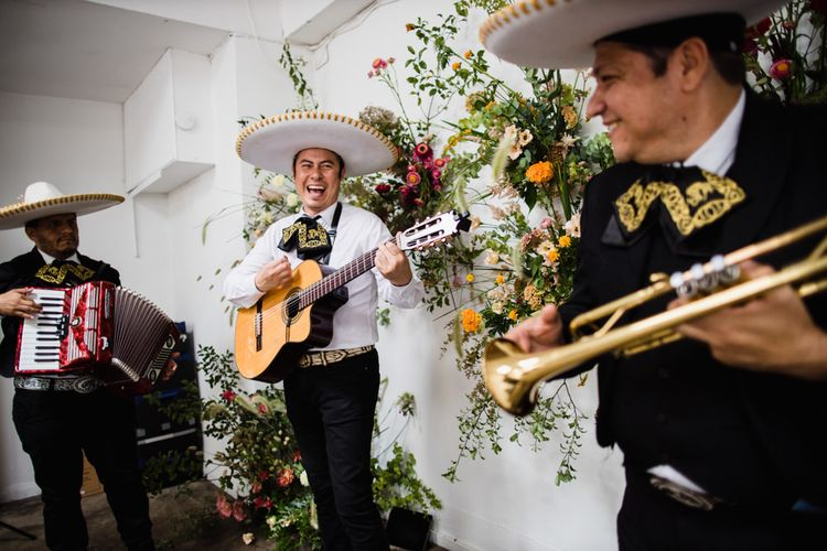 Mariachi band at wedding reception in London with bright floral decor and industrial styling