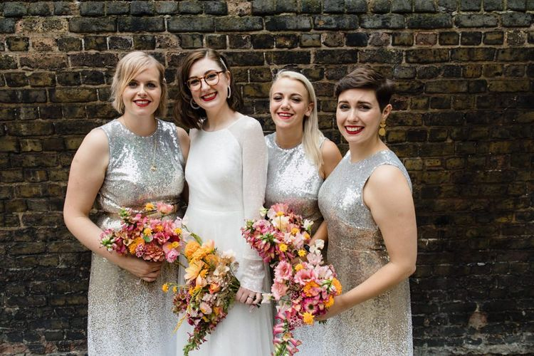 Bride in glasses with her bridesmaids wearing silver sequin dresses and brightly coloured bouquets