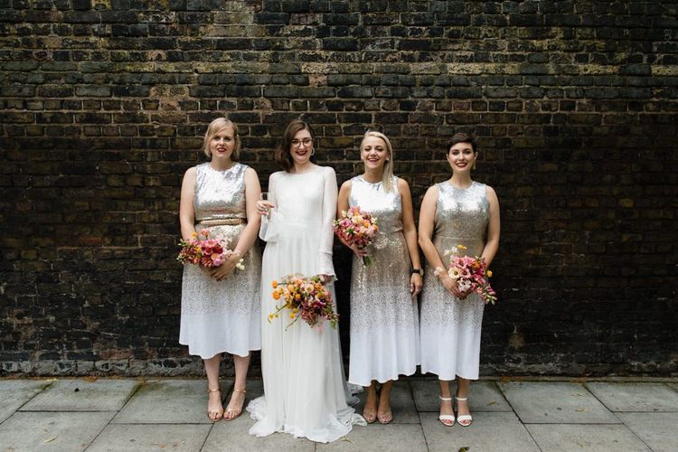 Bride in glasses and long sheer sleeve embellished dress with her bridesmaids wearing silver sequin dresses
