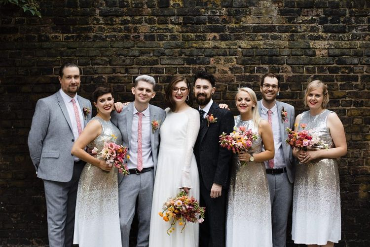 Bride in glasses with her groom and party at industrial wedding in London with bright floral bouquets and embellished dresses