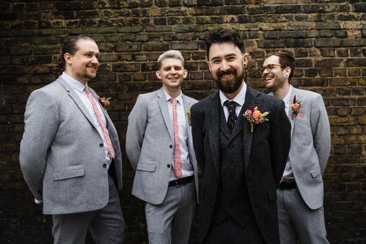 Groom and his groomsmen at industrial wedding in London with bright floral buttonhole and three-piece suit
