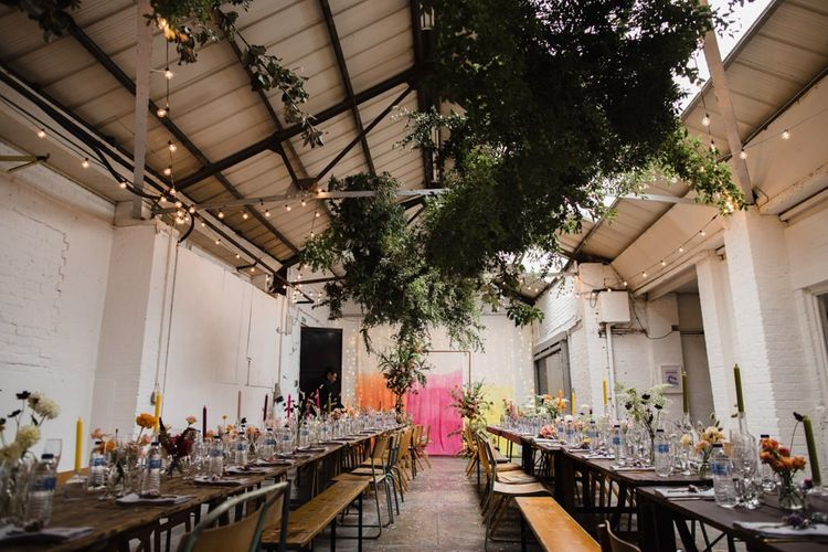 Industrial wedding reception in London with festoon lighting, hanging foliage and bright table decor