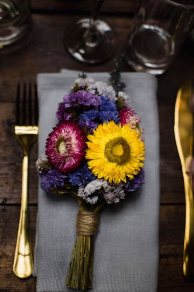 Bright floral table arrangements and gold cutlery at industrial wedding in London
