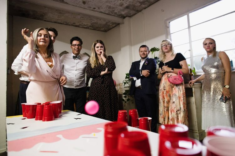 Guests enjoying beer pong at industrial wedding with casual floral decor
