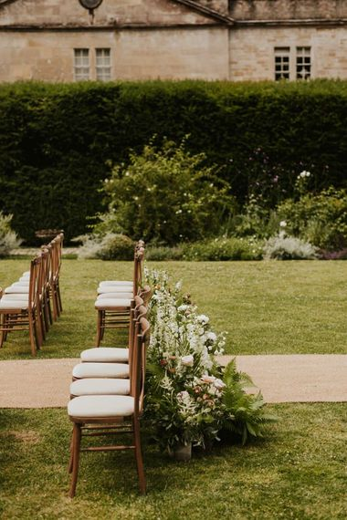aisle chairs and wedding flowers at outdoor ceremony