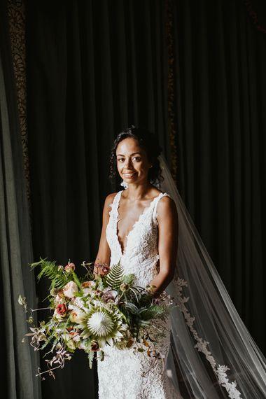 鞋带边缘面纱的新娘拿着婚礼花束与国王蛋白