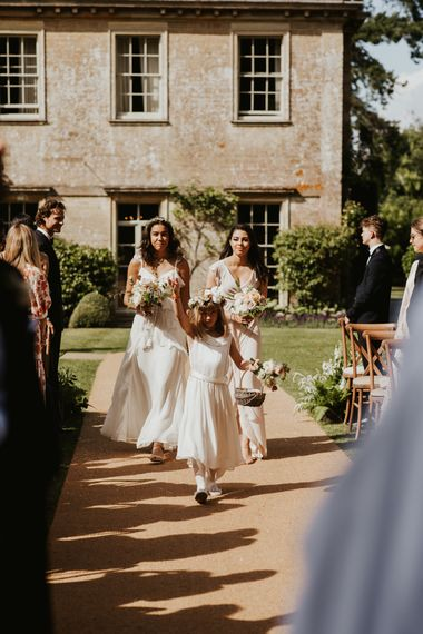 Flower girl and bridesmaids in white dresses walking down the aisle