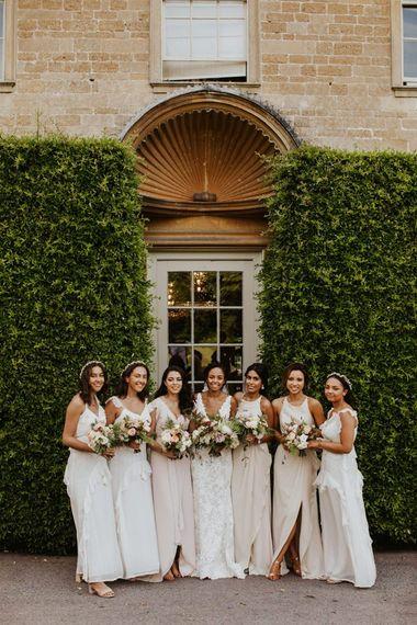 与伴娘的新娘党画象在白色礼服和新娘的鞋带礼服