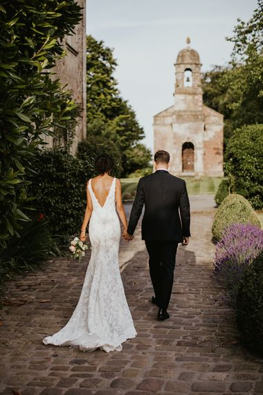 Bride and groom walking through the grounds at Babington House wedding venue