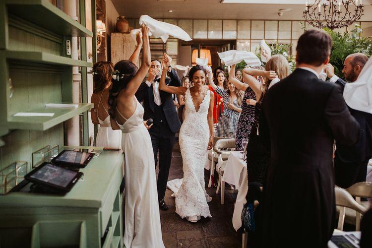 蕾丝婚纱的新娘与挥动他们的餐巾的客人进入婚礼招待会