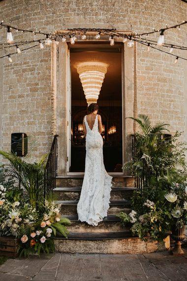 在Pronovias婚礼礼服的新娘走来花的装饰的步在比林顿房子婚礼地点