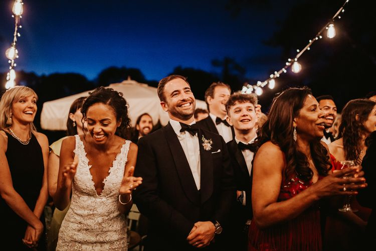Bride and groom laughing during outdoor wedding speeches