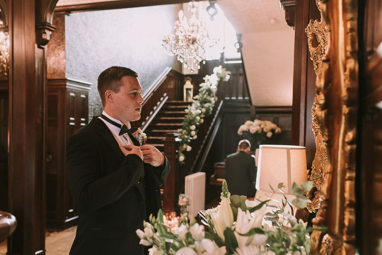 Groom in Tuxedo from Moss Bros. Adjusting His Bow Tie in a Mirror