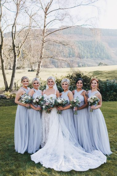 Bridal Party Portrait with Bride in Lace Pronovias Wedding Dress and Bridesmaids in Pale Blue Halterneck Dresses
