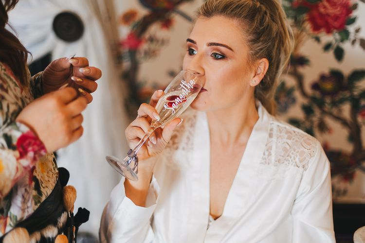 Bride Sipping champagne From Personalised Champagne Flute Whilst Having Her Makeup Done