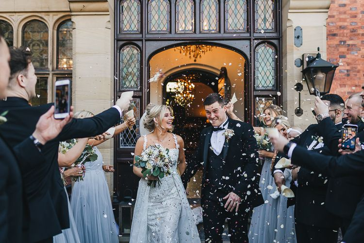 Confetti Moment with Bride in Pronovias 'Edith' Wedding Dress and Groom in Moss Bros. Tuxedo