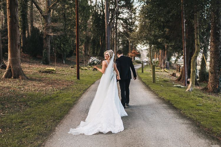 Bride in Pronovias 'Edith' Wedding Dress with Detachable Overskirt and Groom in Moss Bros. Tuxedo Walking Through The Woods