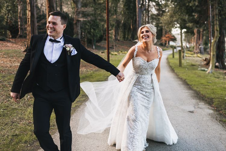 Bride in Pronovias 'Edith' Wedding Dress with Detachable Overskirt and Groom in Moss Bros. Tuxedo Holding Hands Laughing