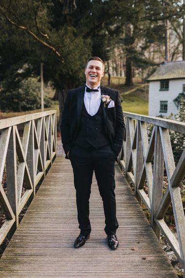 Groom in Black Three-piece Suit  Standing on a Bridge