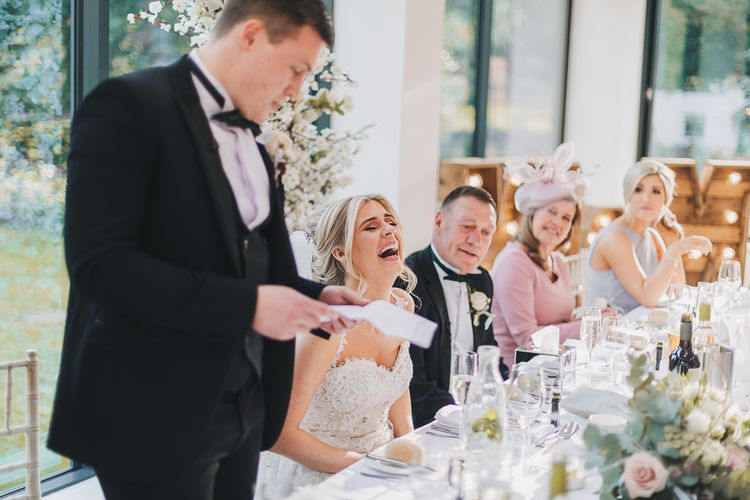Bride in Pronovias Wedding Dress Laughing as Groom in Tuxedo Gives His Wedding Speech