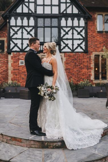 Bride in Lace Wedding Dress with Detachable Skirt and Groom in Black Tie Suit Embracing