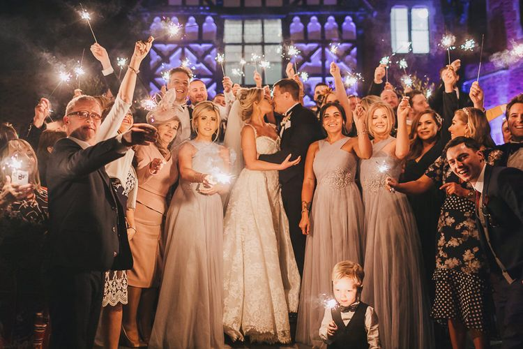 Bride and Groom Surrounded by Wedding Guests Holding Sparklers