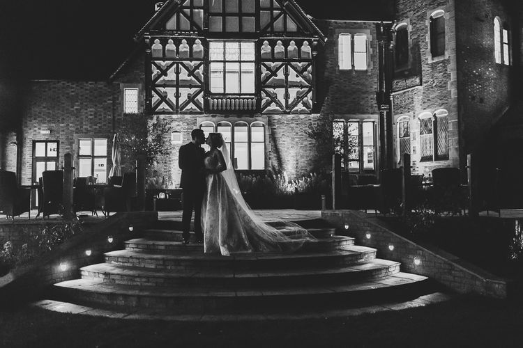 Black and White Portrait of Bride in Lace Wedding Dress with Detachable Skirt and Groom in Black Tie Suit Standing in Front of North Wales wedding venue Tyn Dwr Hall