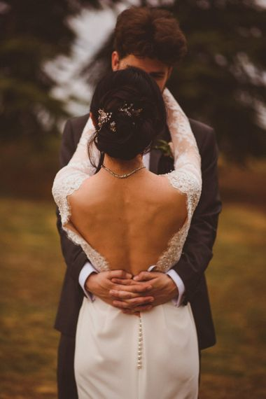 Intimate bride and groom portrait with bride in low back wedding dress
