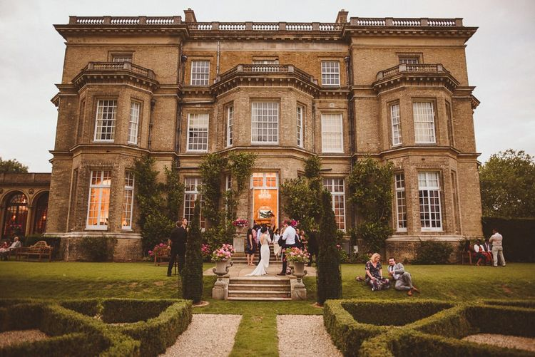 Wedding guests outside at c country house