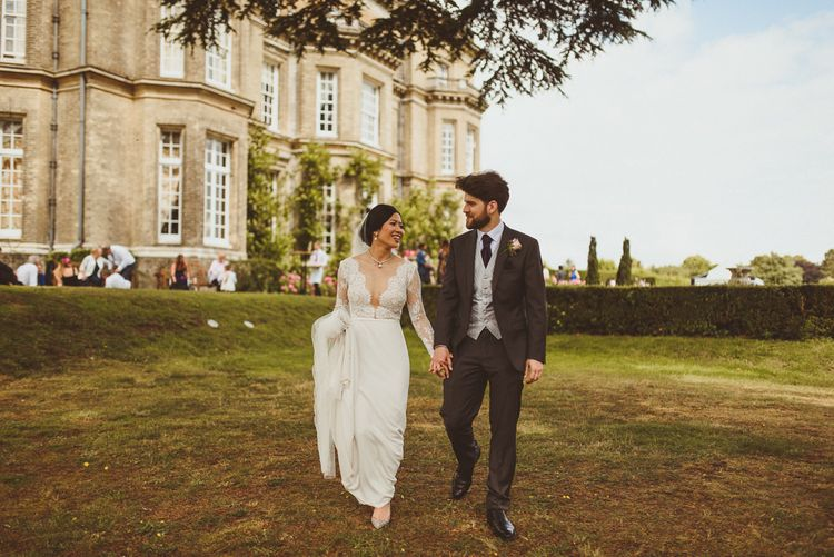 Bride and groom holding hands in Hedsor House gardens