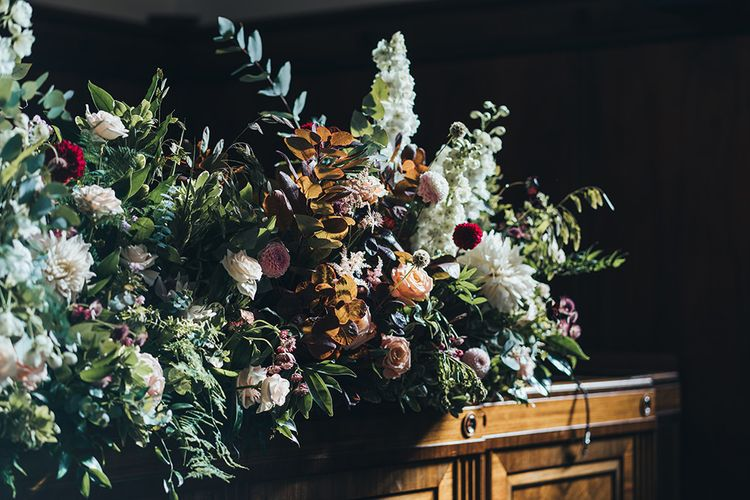 White, apricot and dusky pink flowers at autumn styled wedding reception in East London