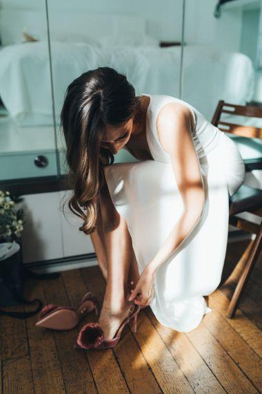 Bride putting on her velvet slingback pom pom shoes