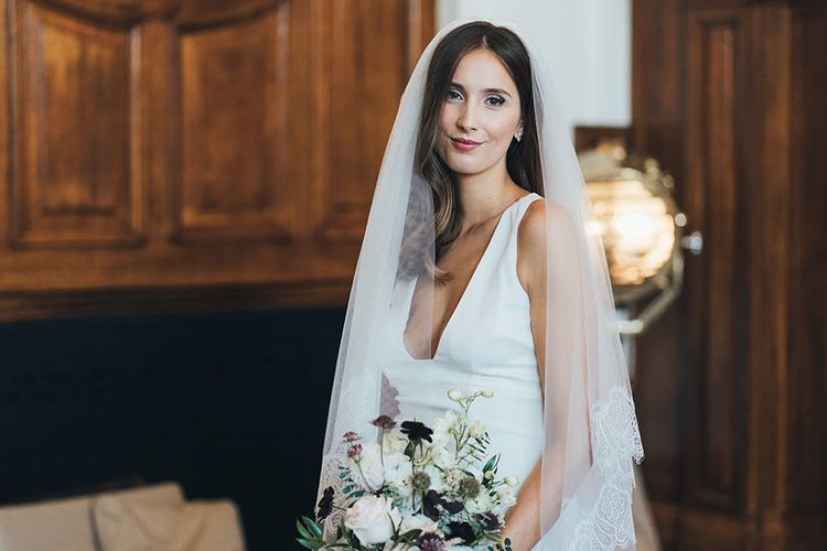 Bride in timeless dress with autumnal bouquet and black bridesmaid dresses