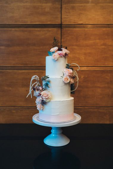 Buttercream wedding cake with dusky pink floral decoration at city wedding reception